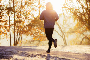 Young man running during autumn, winter morning. Healthy lifestyle concept
